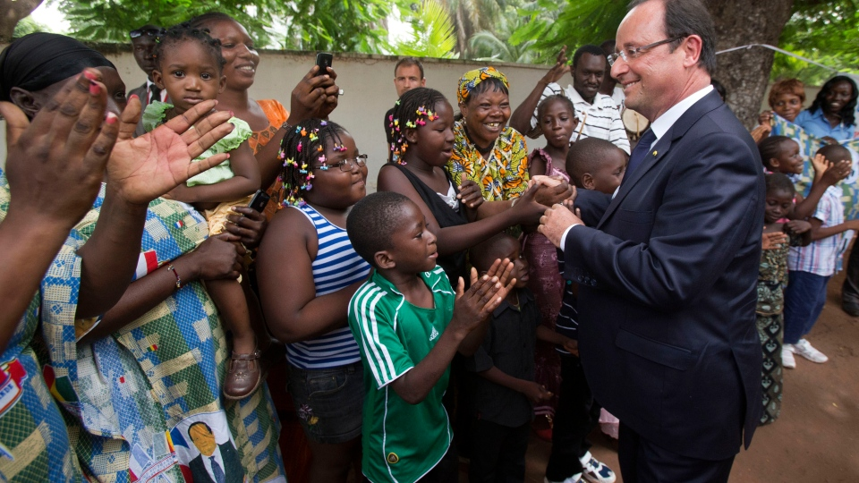 France's President Francois Hollande, right, is welcomed by members of the public outside of the French Ambassadors residence in Bamako, Mali, Thursday, Sept. 19, 2013. (AP / Michel Euler)
