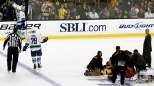 Vancouver Canucks defenseman Aaron Rome is escorted off the ice by linesman Pierre Racicot as medical personnel tend to Boston Bruins right wing Nathan Horton in the first period during Game 3 of the NHL hockey Stanley Cup Finals, Monday, June 6, 2011, in Boston. (AP / Winslow Townson)