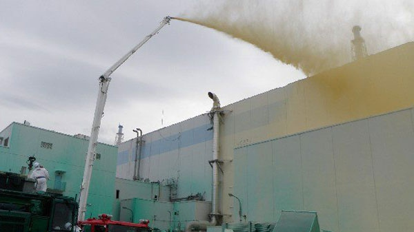 In this Friday, May 27, 2011, photo released by Tokyo Electric Power Co., workers spray a substance to prevent radioactive materials from spreading out from the Unit 1 area at the Fukushima Dai-ichi nuclear complex in Okuma, Fukushima Prefecture, northeastern Japan. (AP / Tokyo Electric Power Co.)