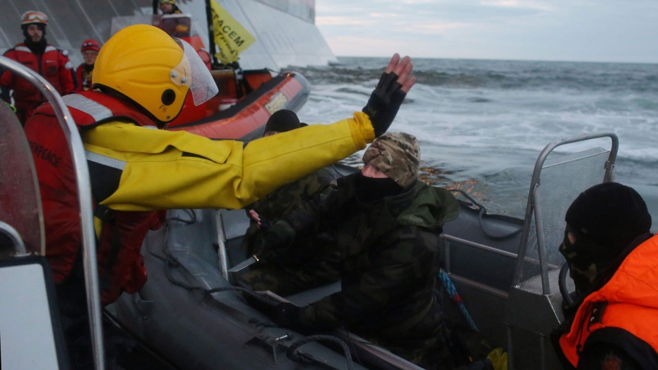A Russian Coast guard officer, centre, is seen pointing a knife at a Greenpeace International activist, left in yellow, as other activists attempt to climb the 'Prirazlomnaya,' an oil platform operated by Russian state-owned energy giant Gazprom platform in Russia's Pechora Sea, a section of the Barents Sea, Wednesday, Sept. 18, 2013.