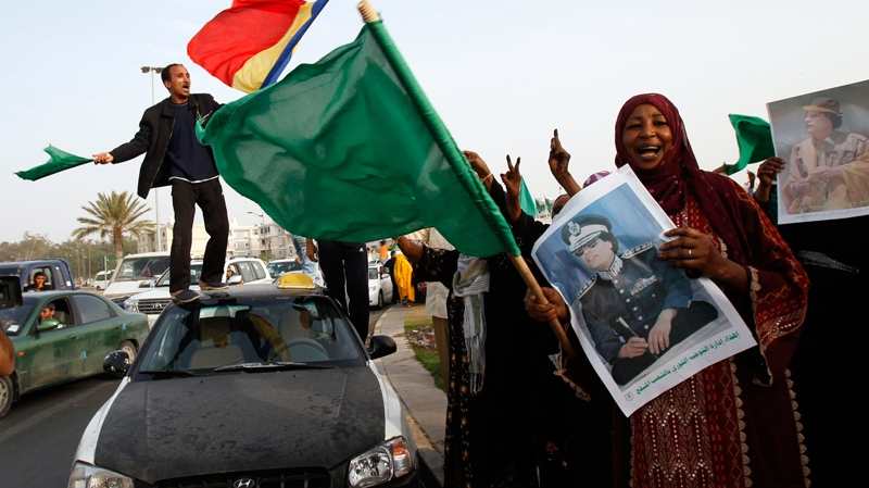 Libyans rally next to Moammar Gadhafi's Bab al-Aziziya compound, a regular target of NATO airstrikes, in Tripoli, Libya, on Tuesday, June 7, 2011. (AP / Ivan Sekretarev)