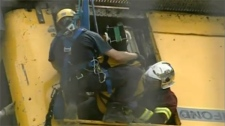 An emergency worker hanging in a harness removes the crane operator - with her head secured - from the cabin.