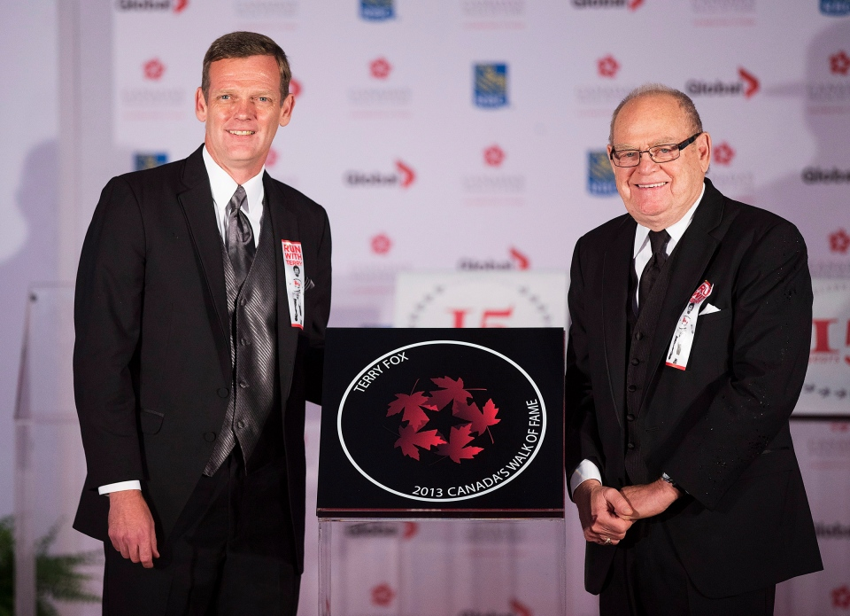 Terry Fox's brother, Darrell, left, and father Rolly, right, pose for a photo during the cancer activist's induction ceremony into Canada's Walk of Fame in Toronto on Saturday, September 21, 2013. (Michelle Siu / THE CANADIAN PRESS)