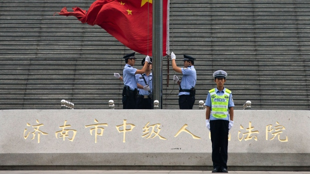 Chinese police officers raise the national flag outside the Jinan Intermediate People's Court in Jinan in eastern China's Shandong province on Sunday, Sept. 22, 2013. (AP / Andy Wong)