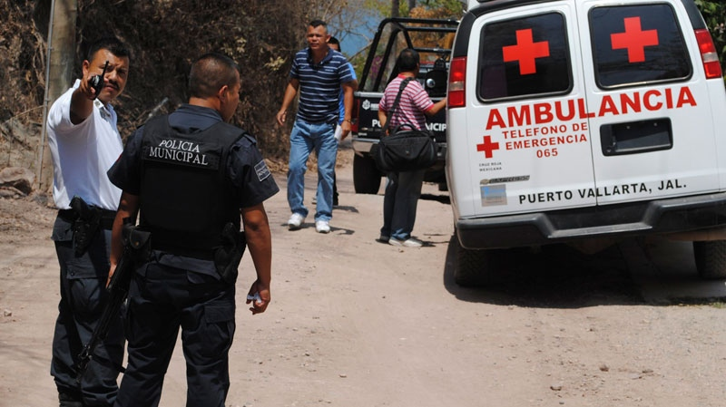 In this photo taken May 30, 2011, municipal police stand outside the home of 62-year-old Canadian citizen Leonard Francis Schell after he was found dead, stabbed repeatedly by unidentified assailants, in the Mexican Pacific resort city of Puerto Vallarta, Mexico. (AP Photo)