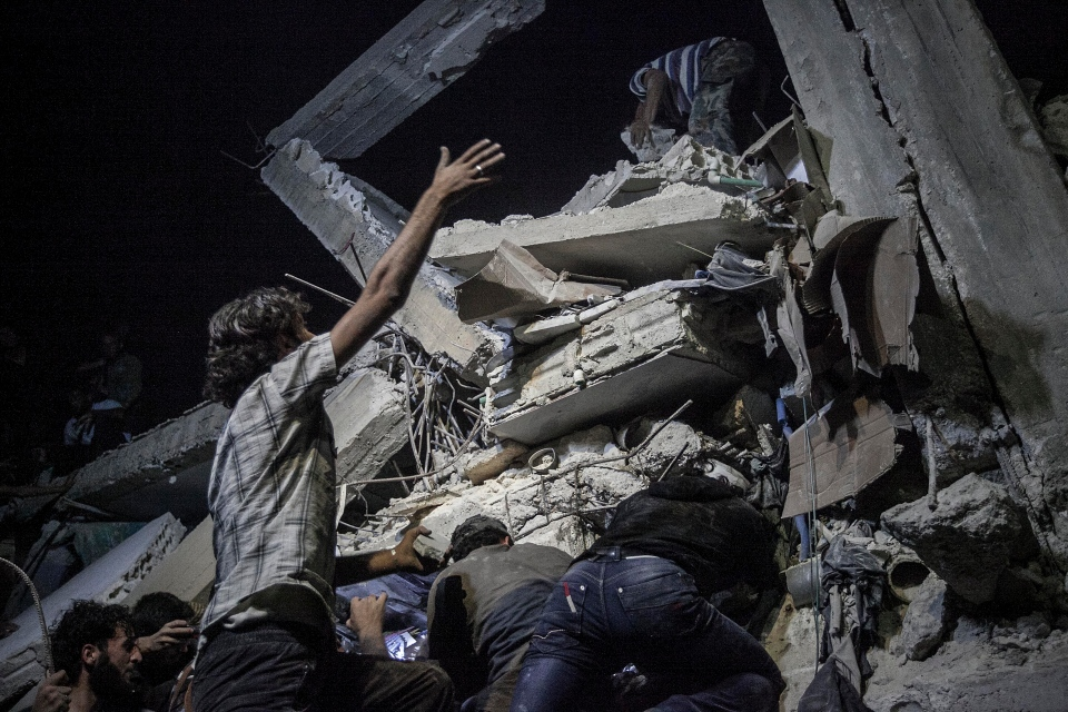 Syrian villagers remove debris as they try to rescue victims, not pictured, of a building destroyed due to an airstrike that hit a village turned into a battlefield between government forces and Free Syrian Army fighters in Idlib province, northern Syria, Sunday, Sept. 22, 2013. (AP)
