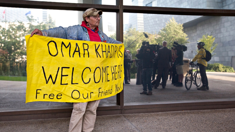 A supporter holds a sign and stands outside the Edmonton courthouse during former Guantanamo Bay inmate Omar Khadr's court appearance in Edmonton, on Monday, Sept. 23, 2013. (Jason Franson / THE CANADIAN PRESS)
