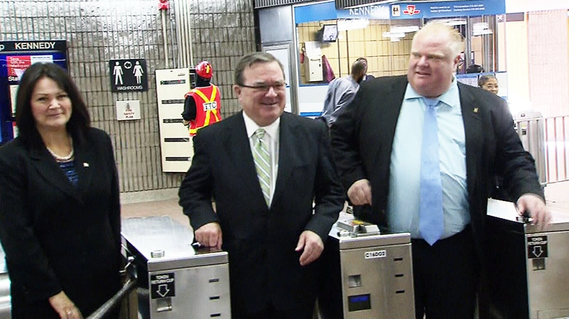Finance Minister Jim Flaherty, centre, and Toronto Mayor Rob Ford, right, pose at Kennedy Station in Toronto on Monday, Sept. 23, 2013.