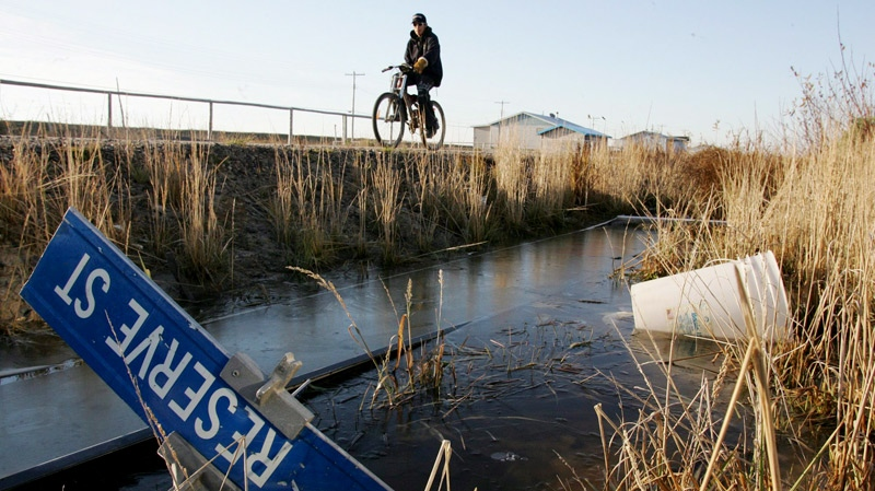 Kenny Wynne rides his bike along a road on the Kashechewan native reserve in northern Ontario on Oct. 28, 2005. (Jonathan Hayward / THE CANADIAN PRESS)