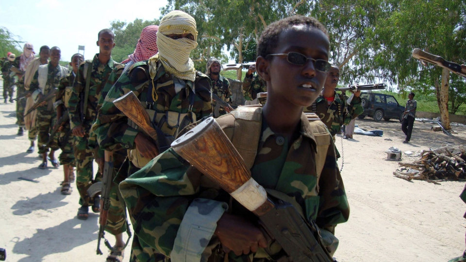 A young boy leads the hard-line Islamist Al Shabab fighters as they conduct military exercise in northern Mogadishu's Suqaholaha neighborhood, Somalia, Friday, Jan. 1, 2010. (AP / Farah Abdi Warsameh)