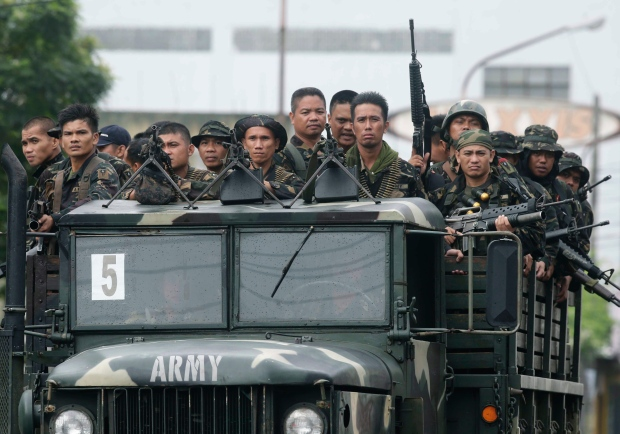 Government troopers arrive to reinforce their comrades after an army officer was killed in the ongoing operation against Muslim rebels, on Thursday Sept. 19, 2013, the 11th day of the standoff in Zamboanga city in southern Philippines.  (AP /Bullit Marquez)