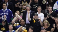 Prime Minister Stephen Harper, centre, attends game 4 of the NHL Stanley Cup Final hockey action between the Vancouver Canucks and the Boston Bruins at the TD Garden in Boston on Wednesday, June 8, 2011.  (Jonathan Hayward / THE CANADIAN PRESS)
