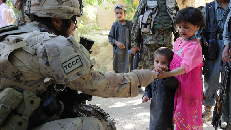 A Canadian Forces soldier hands food to Afghan children during an early morning operation into the village of Haji Baran Afghanistan, on June 4, 2011. (Combat Camera / Sgt. Matthew McGregor)