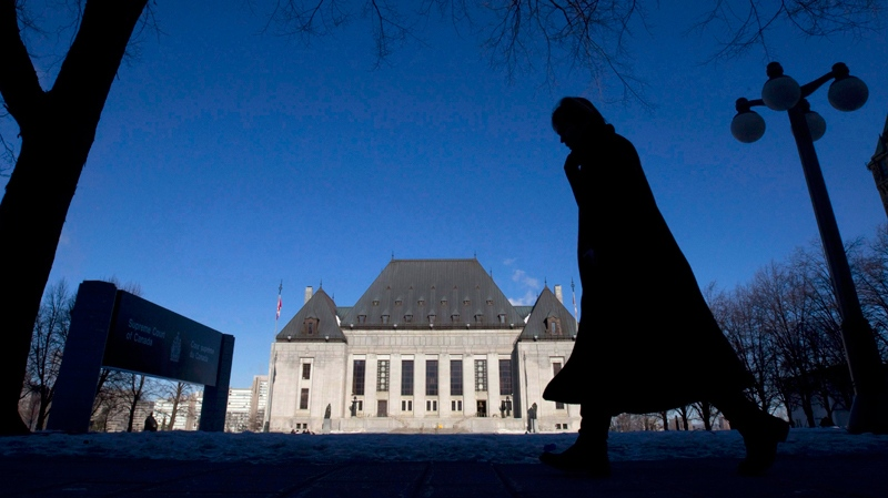 A pedestrian is shown walking past the Supreme Court of Canada in Ottawa, Wednesday Feb. 23, 2011. (Adrian Wyld / THE CANADIAN PRESS)