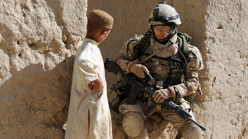 A young Afghan boy attempts to communicate with Corporal Marie-Anne Hardy as she takes a break during an early morning operation into the village of Haji Baran, Afghanistan, on June 4, 2011. (Combat Camera / Sgt. Matthew McGregor)