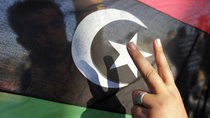 A Libyan flashes the victory signs in front of a rebel flag aboard a ship in Misrata port, Libya, Friday, June 10, 2011. (AP Photo/Hassan Ammar)