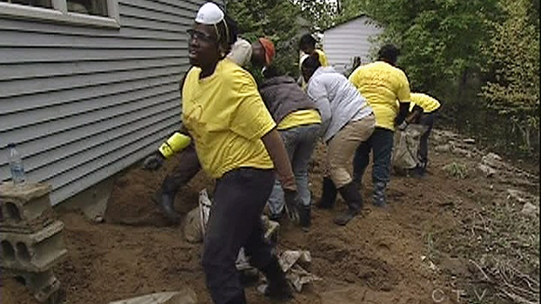 Volunteers from a church group are shown helping with the cleanup efforts in flood-ravaged areas south of Montreal on Saturday, June 11, 2011.