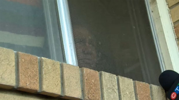 A man talks to reporters though a side window of the Parkdale duplex on Friday, Sept. 27, 2013.