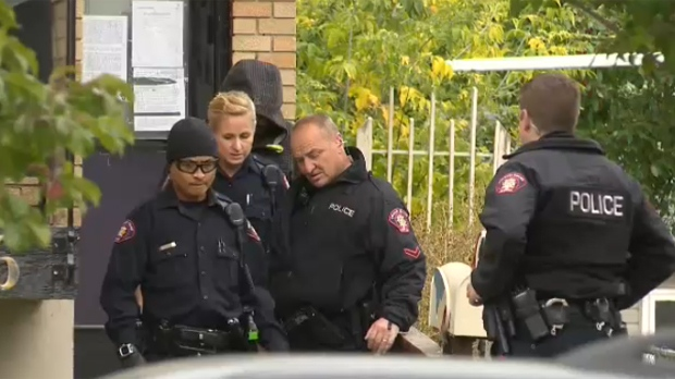 CPS officers escort an unidentified person from the Parkdale duplex