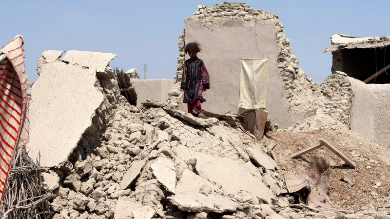 A Pakistani girl walks on the rubble of a house destroyed following an earthquake in Labach, the remote district of Awaran in Baluchistan province, Pakistan, Thursday, Sept. 26, 2013. Officials say another major earthquake hit the region Saturday, Sept. 28, 2013. (AP / Shakil Adil)