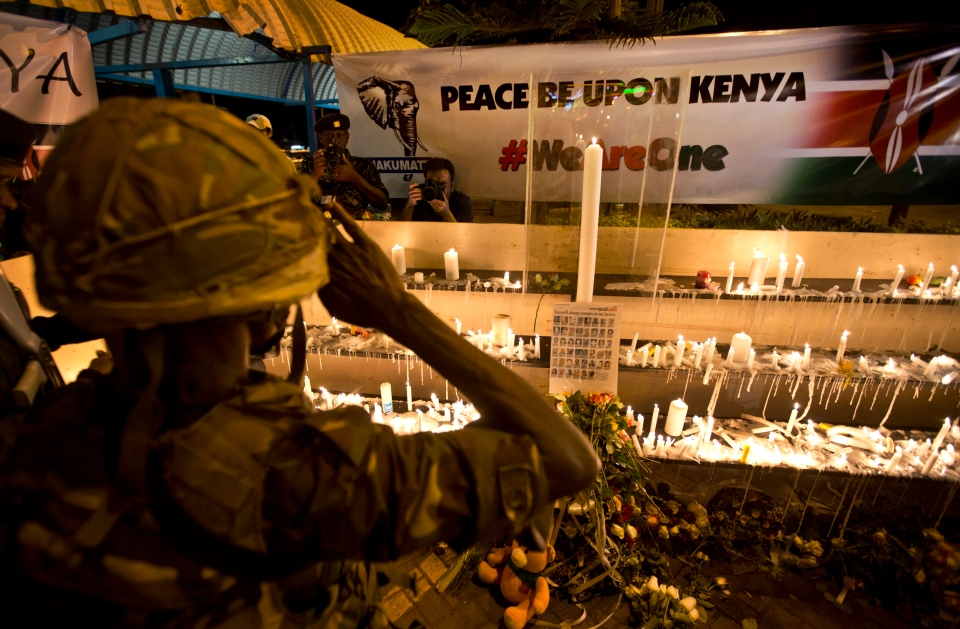 A soldier from the Kenya Defence Forces salutes to pay his respects as he and other Kenyans came to light candles, sing and pray, marking one week since the terrorist attack that killed 67 people, in front of the Westgate Mall in Nairobi, Kenya Saturday, Sept. 28, 2013. (AP / Ben Curtis)