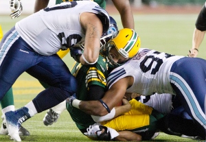 Toronto Argonauts' Cleyon Laing (90) and Ivan Brown (97) hit Edmonton Eskimos quarterback Mike Reilly (13) during first half action in Edmonton, Alta., on Saturday September 28, 2013.  (Jason Franson /The Canadian Press)