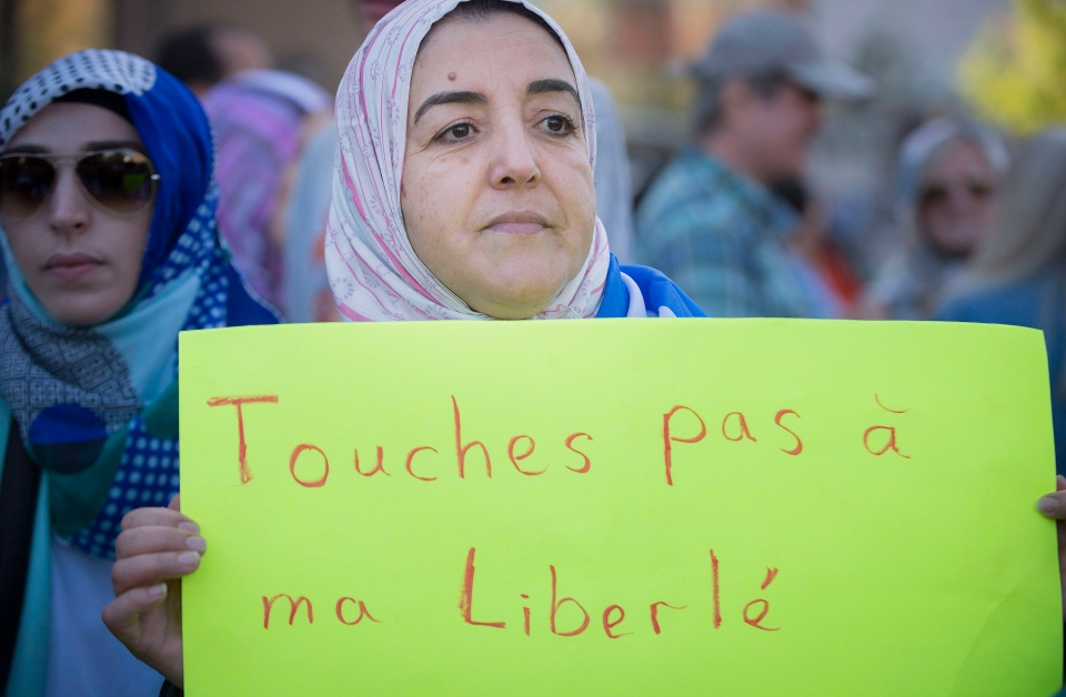 A protester holds a sign asking that no one touch her freedoms during a protest in Montreal against the proposed charter of values by the Parti Quebecois, Sunday, Sept. 29, 2013. (Peter McCabe / THE CANADIAN PRESS)