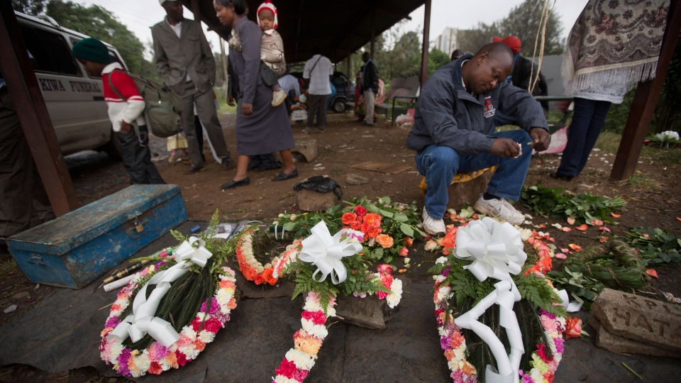 A street-trader makes floral wreaths outside the mortuary in Nairobi, Kenya., Wednesday, Sept. 25, 2013.  (AP / Ben Curtis)
