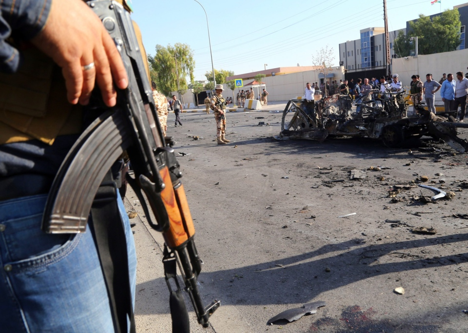 Kurdish security forces and citizens inspect the site of a car bomb attack in front of the main security forces headquarters in Irbil, Iraq, Sunday, Sept. 29, 2013. (AP)