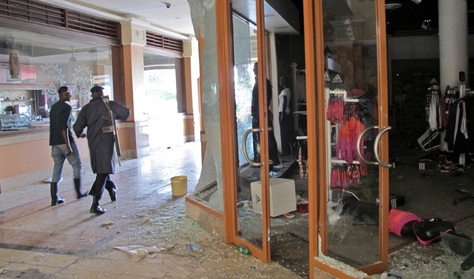 An armed policeman walks past the shattered glass windows of a shop in the Westgate Mall in Nairobi, Kenya on Tuesday, Oct. 1, 2013. (AP / Rukmini Callimachi)