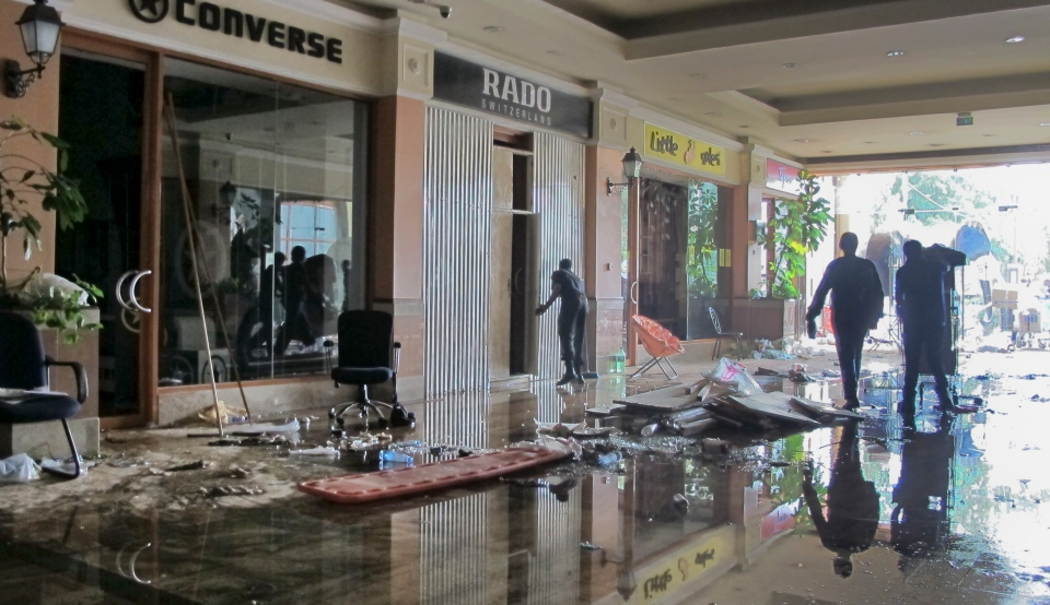 People clean up the mess at damaged shops next to the main entrance of the Westgate Mall in Nairobi, Kenya Tuesday, Oct. 1, 2013. (AP / Rukmini Callimachi)