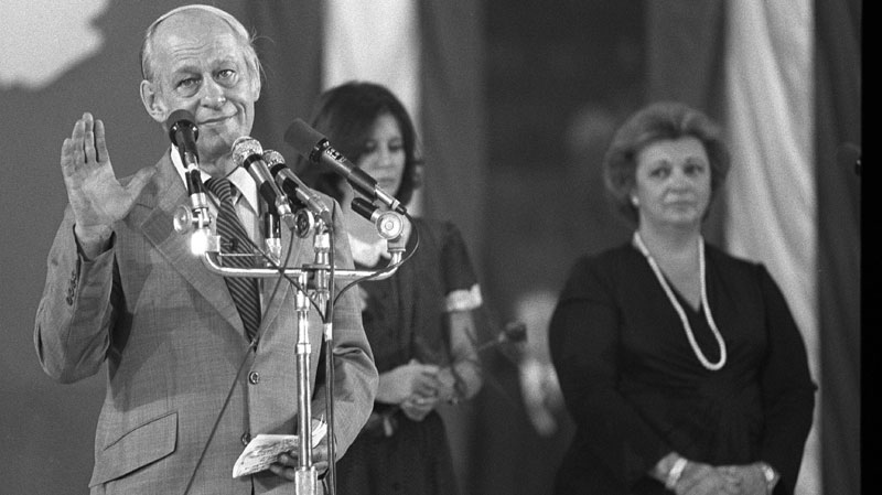 Premier Rene Levesque tries to quiet the crowd in Montreal's Paul Sauve Arena before conceding defeat on May 20, 1980 in the Quebec referendum, as his wife Corinne (centre) and Lise Payette look on from the background. (THE CANADIAN PRESS/file)