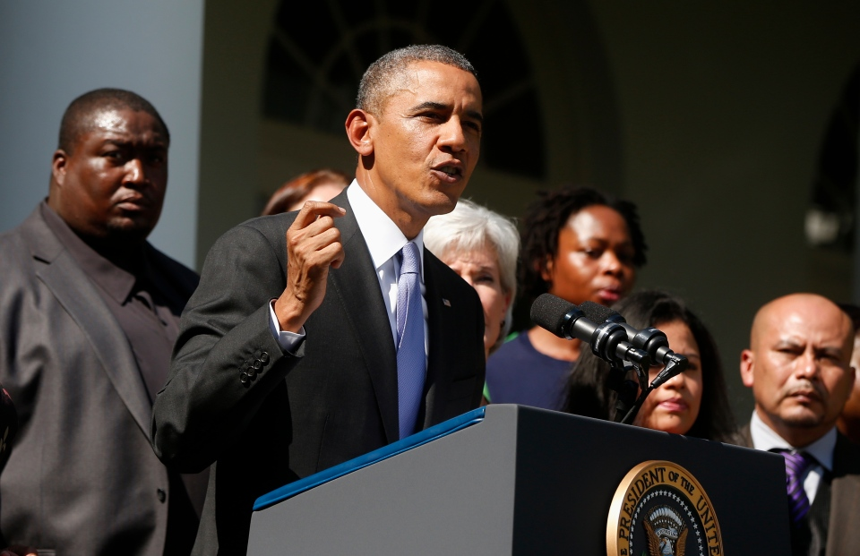 U.S. President Barack Obama stands with people who support the Affordable Care Act, his signature health care law, as he speaks in the Rose Garden of the White House in Washington, Tuesday, Oct. 1, 2013. (AP / Charles Dharapak)