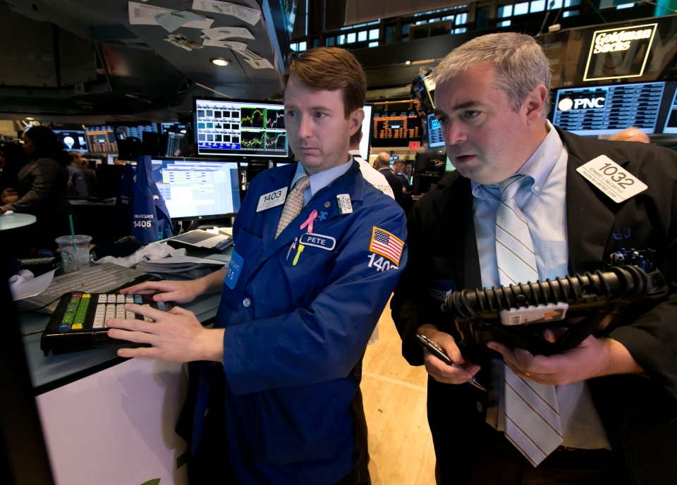 Specialist Peter Elkins, left, and trader Edward McCarthy work on the floor of the New York Stock Exchange Wednesday, Oct. 2, 2013. (AP / Richard Drew)