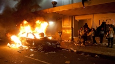A car burns outside The Bay department store during a riot in downtown Vancouver, Wednesday, June 15, 2011 following the Vancouver Canucks 4-0 loss to the Boston Bruins in game 7 of the Stanley Cup hockey final. (Ryan Remiorz / THE CANADIAN PRESS)