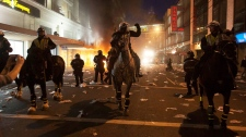 Police on horseback move down a street during a riot in downtown Vancouver, Wednesday, June 15, 2011. THE CANADIAN PRESS / Ryan Remiorz