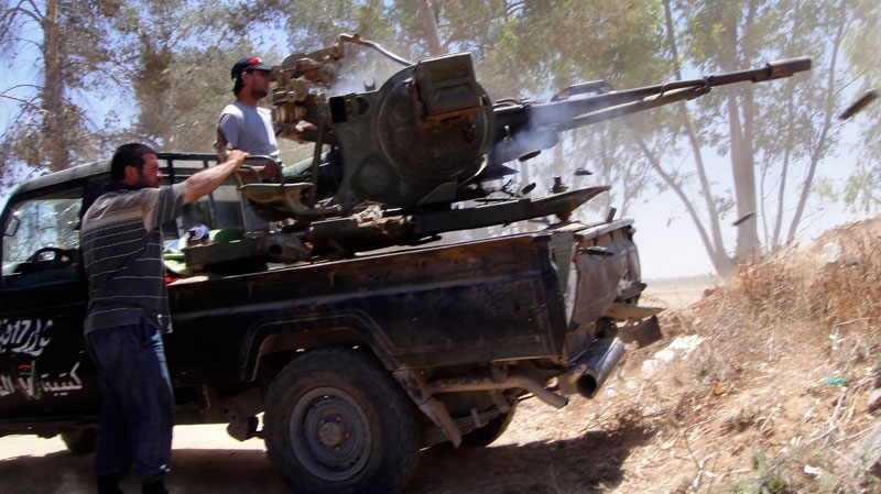 Rebel fighters fire their machine guns towards pro-Moammar Gadhafi forces at the front line of Dafniya, west of Misrata, Libya, Wednesday, June 15, 2011. (AP / Hassan Ammar)