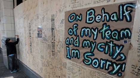 A woman writes a message on plywood covering the windows of the damaged Hudson's Bay Company store in Vancouver, B.C., on Thursday June 16, 2011, after the store was damaged and looted by rioters following the Vancouver Canucks loss to the Boston Bruins in the NHL's Stanley Cup Final Wednesday night. THE CANADIAN PRESS/Darryl Dyck