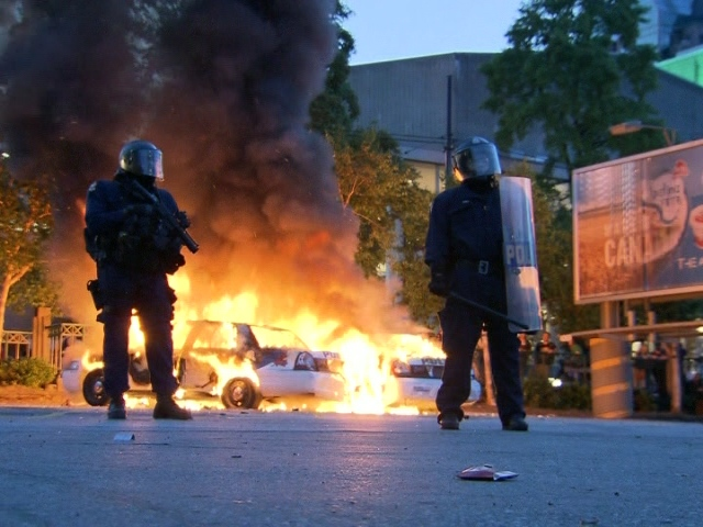 Officers stand guard over two burning police cruisers following the Vancouver Canucks 4-0 loss to the Boston Bruins in Game 7 of the Stanley Cup hockey final, in Vancouver, Wednesday, June 15, 2011.