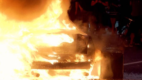 A car blazes outside The Bay in downtown Vancouver. June 15, 2011. (CTV)