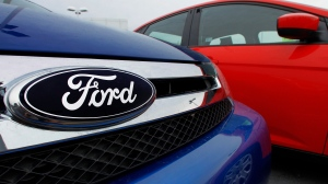 The Ford logo is seen on cars for sale at a Ford dealership in Springfield, Ill. on July 1, 2012. (AP / Seth Perlman)