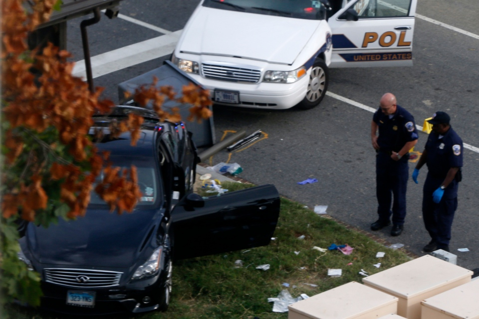 Police officers look at a car following a shooting on Capitol Hill in Washington, Thursday, Oct. 3, 2013. (AP / Charles Dharapak)