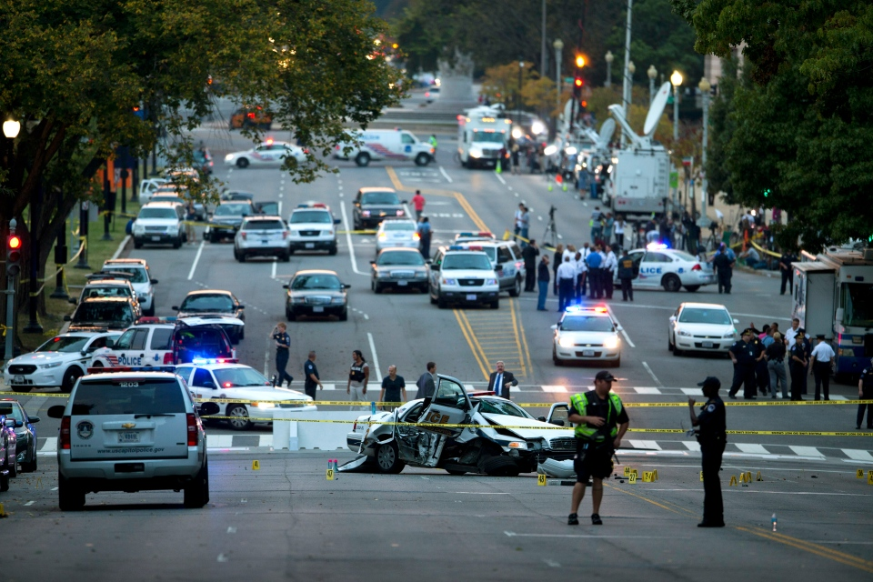 A damaged Capitol Hill police car is surrounded by crime scene tape on Constitution Avenue near the U.S. Capitol after a car chase and shooting in Washington, Thursday, Oct. 3, 2013. (AP / Evan Vucci)