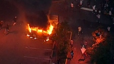 Rioters watch as a vehicle burns in Vancouver on Wednesday, June 15, 2011.