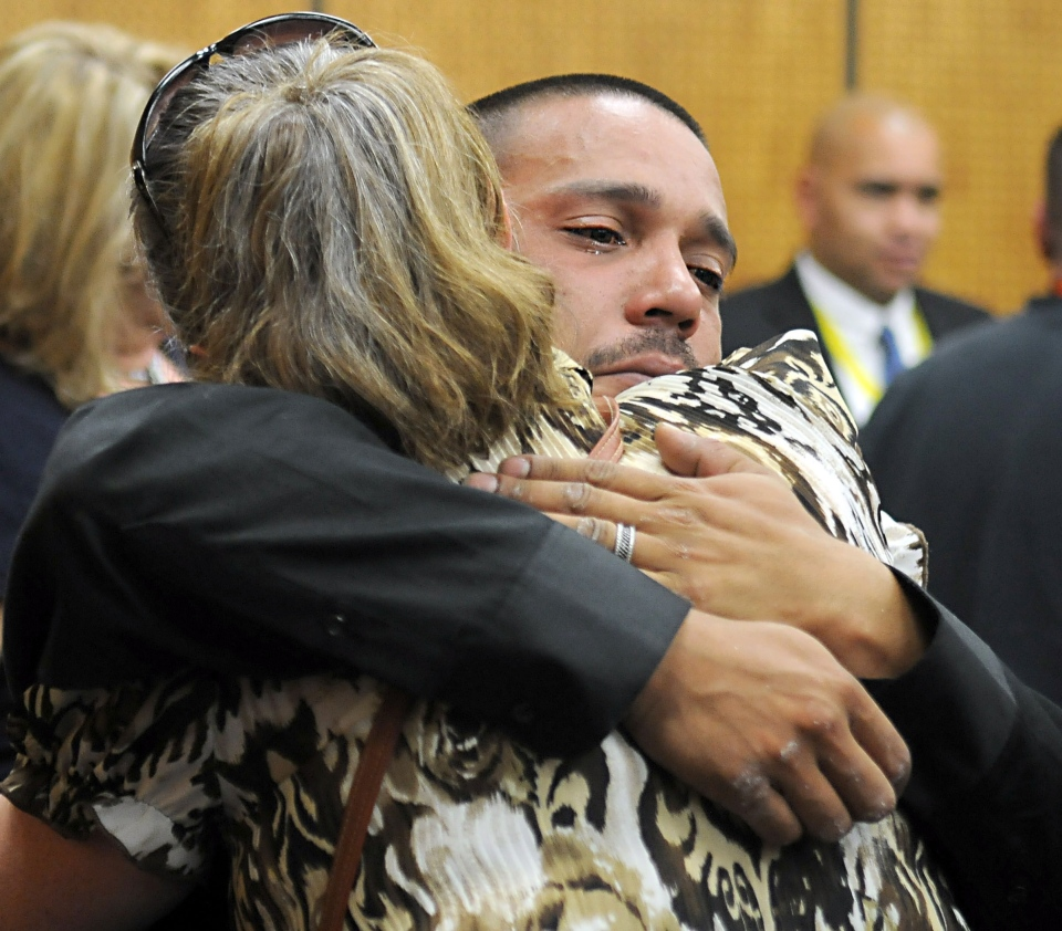 A tearful Josh Pettigrew of San Jose, Calif., hugs his aunt, Jeanine Pettigrew Moreno after his uncle's killer was sentenced to life Thusday Oct. 3, 2013, in Reno, Nev. (The Reno Gazette-Journal, Marilyn Newton)