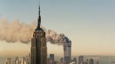 FILE- This Sept. 11, 2001 file photo shows the twin towers of the World Trade Center burning behind the Empire State Building in New York. The book world plans a low-key remembrance of the upcoming 10th anniversary of the Sept. 11 terrorist attacks.