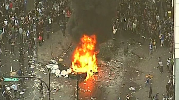 Angry fans add material to a burning fire in Vancouver after the Canucks lost game seven of the Stanley Cup Finals on Wednesday, June 15, 2011.