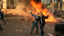 Rioters pose in front of a large fire during a riot following the Vancouver Canucks 4-0 loss to the Boston Bruins in game 7 of the Stanley Cup hockey final in Vancouver, Wednesday, June 15, 2011.
