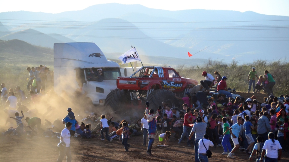 People run as an out of control monster truck plows through a crowd of spectators at a Mexican air show in the city of Chihuahua, Mexico, Saturday Oct. 5, 2013. (El Diario de Chihuahua)