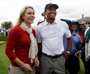 United States team player Tiger Woods, right, smiles with girlfriend Lindsey Vonn after U.S. won the Presidents Cup golf tournament at Muirfield Village Golf Club Sunday, Oct. 6, 2013, in Dublin, Ohio. (AP Photo/Darron Cummings)